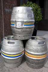 Three empty metal kegs outside a bar