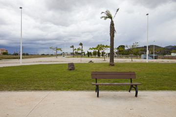 Bench in park with stormy sky, Valencia region, Spain