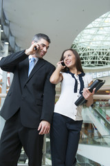 Businessman and businesswoman on mobile phones