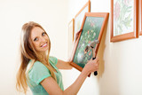 Happy blonde woman hanging  picture with flowers