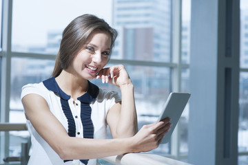 Pensive businesswoman smiling at camera holding digital tablet