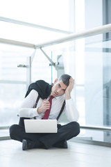 Stressed out businessman seated on floor working at laptop