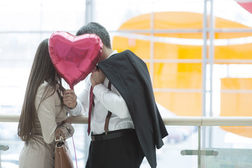 Man and woman kiss behind heart shaped balloon