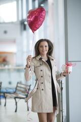Woman runs to camera holding heart shaped balloon and gift