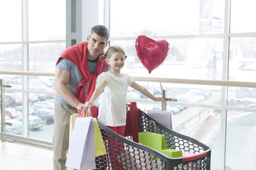 Father pushing young daughter in shopping trolley with shopping bags