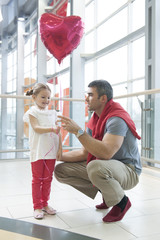 Father gives young daughter heart shaped balloon