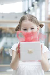 Young girl handing present towards camera