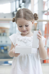 Young girl opens white box and looks into it