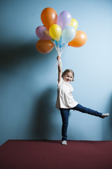 Young girl holds bunch of colorful balloons