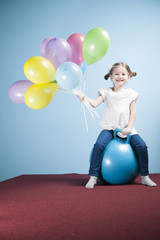Young girl holding balloons on a hoppity horse
