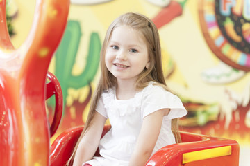 Young girl sitting on childrens car ride