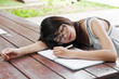 Beautiful Asian student woman tired and sleep.