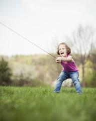 Young girl playing tug of war