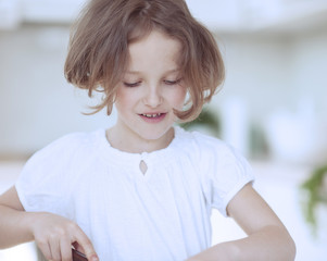 Close-up portrait of young girl chopping food in kitchen