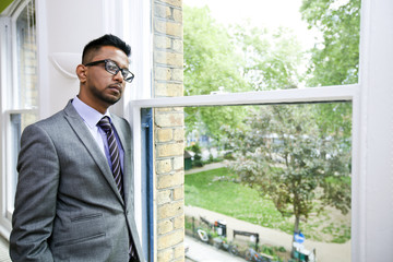 Portrait of Indian Businessman wearing glasses standing by the window