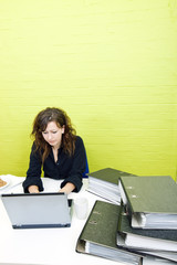 Caucasian young woman working on her laptop computer at her desk