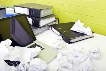 Close-up view of crumpled paper over laptop on desk with empty chair and folders