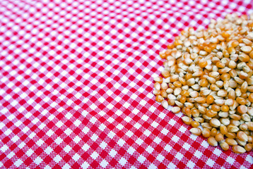 Corn kernels close up on a red and white tablecloth
