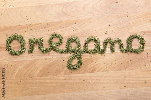 Word Oregano written on wooden table