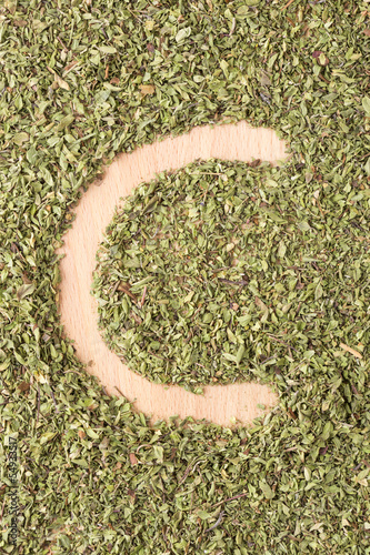 Letter C written with oregano