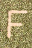 Letter F written with oregano