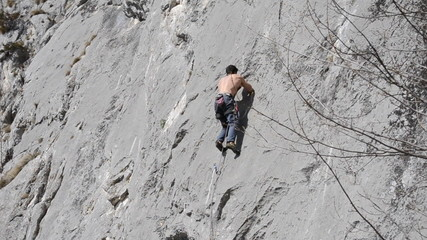 Rock climber climbing difficult route on limestone cliff