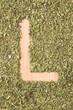 Letter L written with oregano