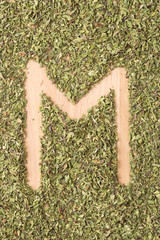 Letter M written with oregano