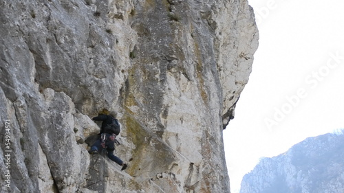 Rock climber struggling to climb difficult route