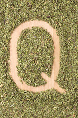 Letter Q written with oregano