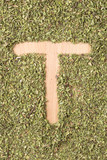 Letter T written with oregano