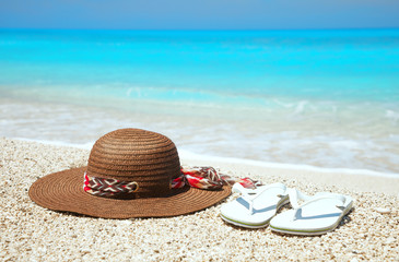 Hat and flip flops on a beach