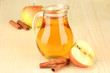 Full jug of apple juice and apple on wooden background