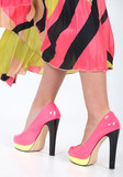 Stylish pink high heels with a green yellow trim