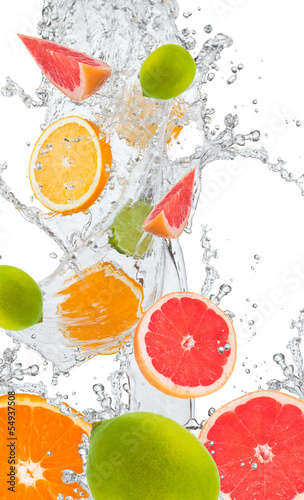 Fresh oranges, lime amd grapefruits falling in water splash