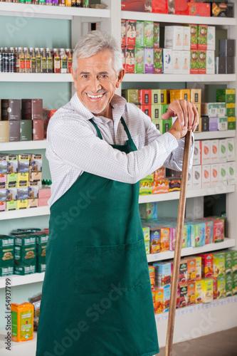 Senior Male Owner Standing Against Shelves In Supermarket