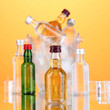 Minibar bottles in bucket with ice cubes,  on color background