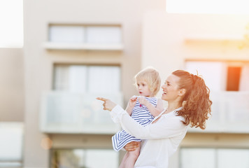 Happy mother with baby standing in front of house building