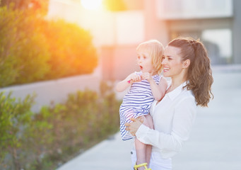 Happy mother and baby in front of house building