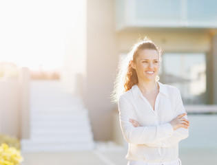 Portrait of happy woman standing in front of house building