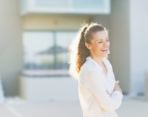 Portrait of laughing woman standing in front of house building