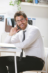 Young businessman talking on smartphone in office.