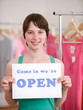 Store owner holding open sign