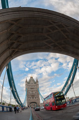 Red bus passing through the Tower Bridge in London.