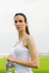 Young beautiful woman drinking water after fitness exercise