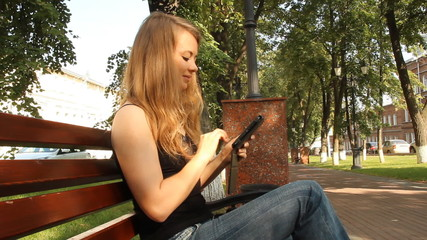 A young girl in a park with a tablet computer. summer