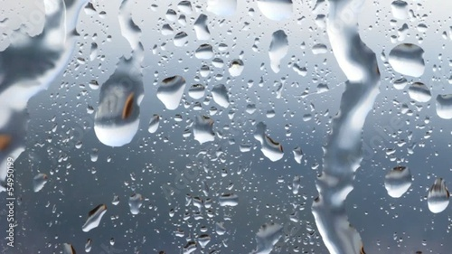 Flowing down water drops on glass.