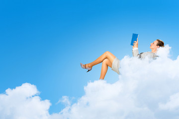 Businesswoman lying on clouds