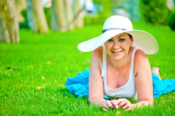 young beautiful smiling girl relaxing on the lawn in a white hat