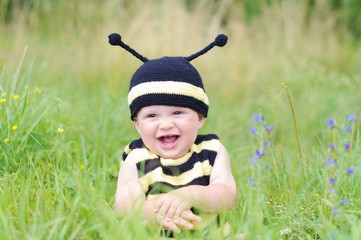 baby in bee costume on the meadow